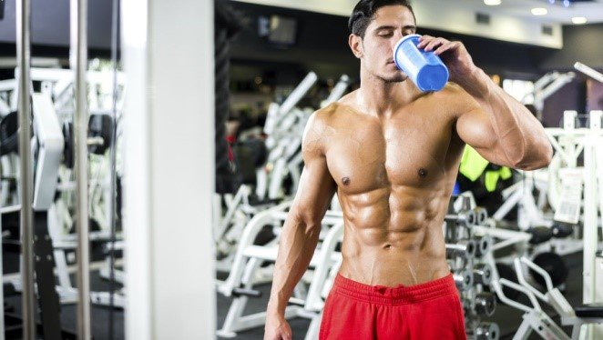An athlete drinking supplements in the gym