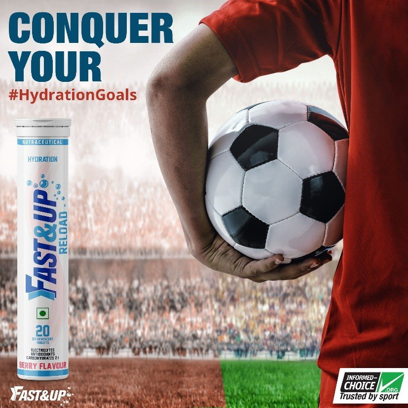 A footballer holding a football in his hand inside a full stadium with Fast&Up Reload tube kept beside him