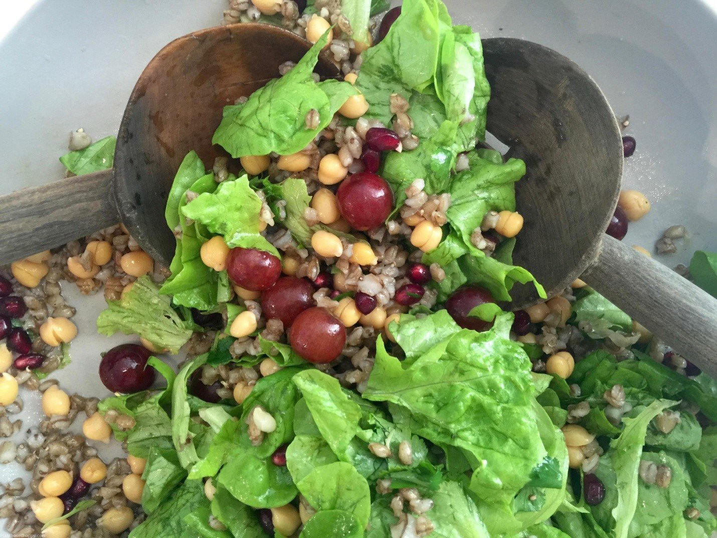 A spatula mixing Lettuce, grapes, chickpeas