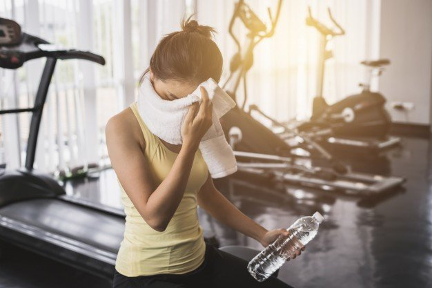 A tired female athlete in front of a treadmill