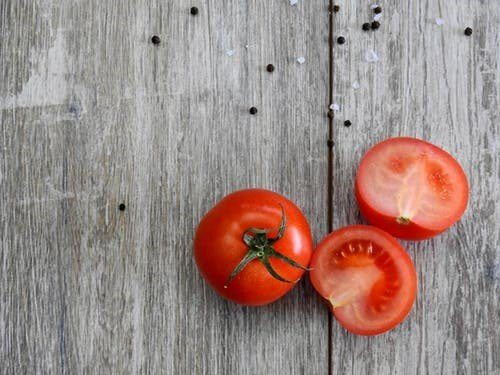 A round tomato and a sliced tomato on a table