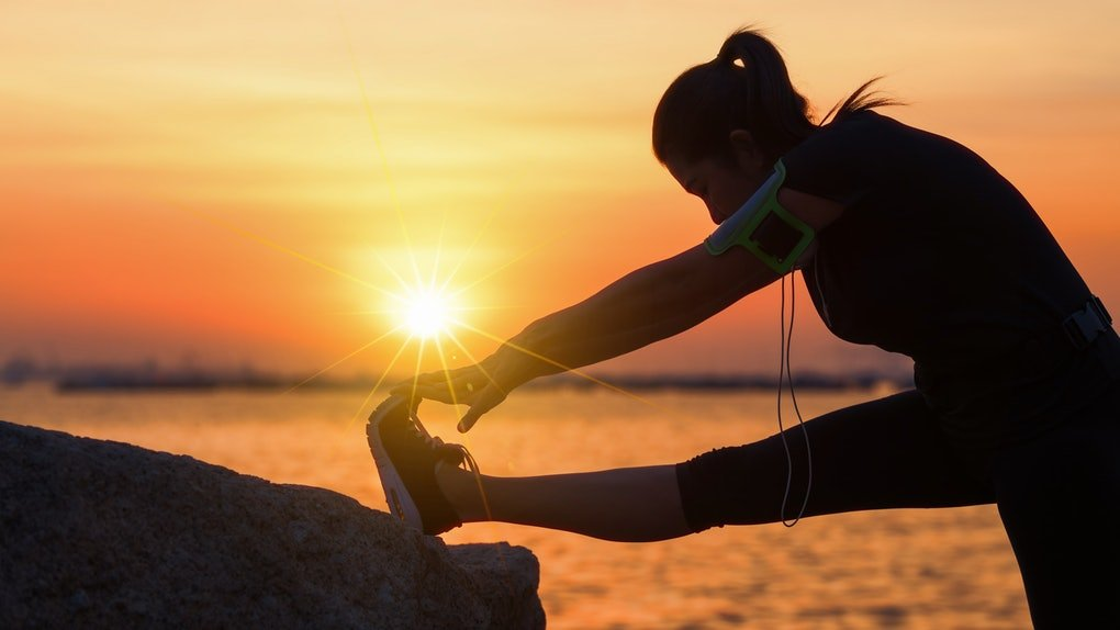 A female athlete stretching while the sun is rising