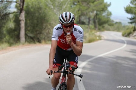 A professional cyclist cycling and drinking energy gel