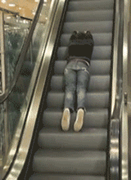 A person lying on the escalator